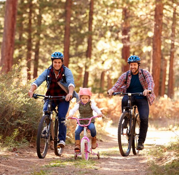 family biking trough a forest