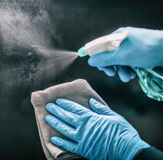 Hands cleaning a dark surface