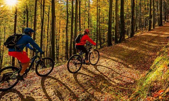 couple mountain biking in Maine in forest