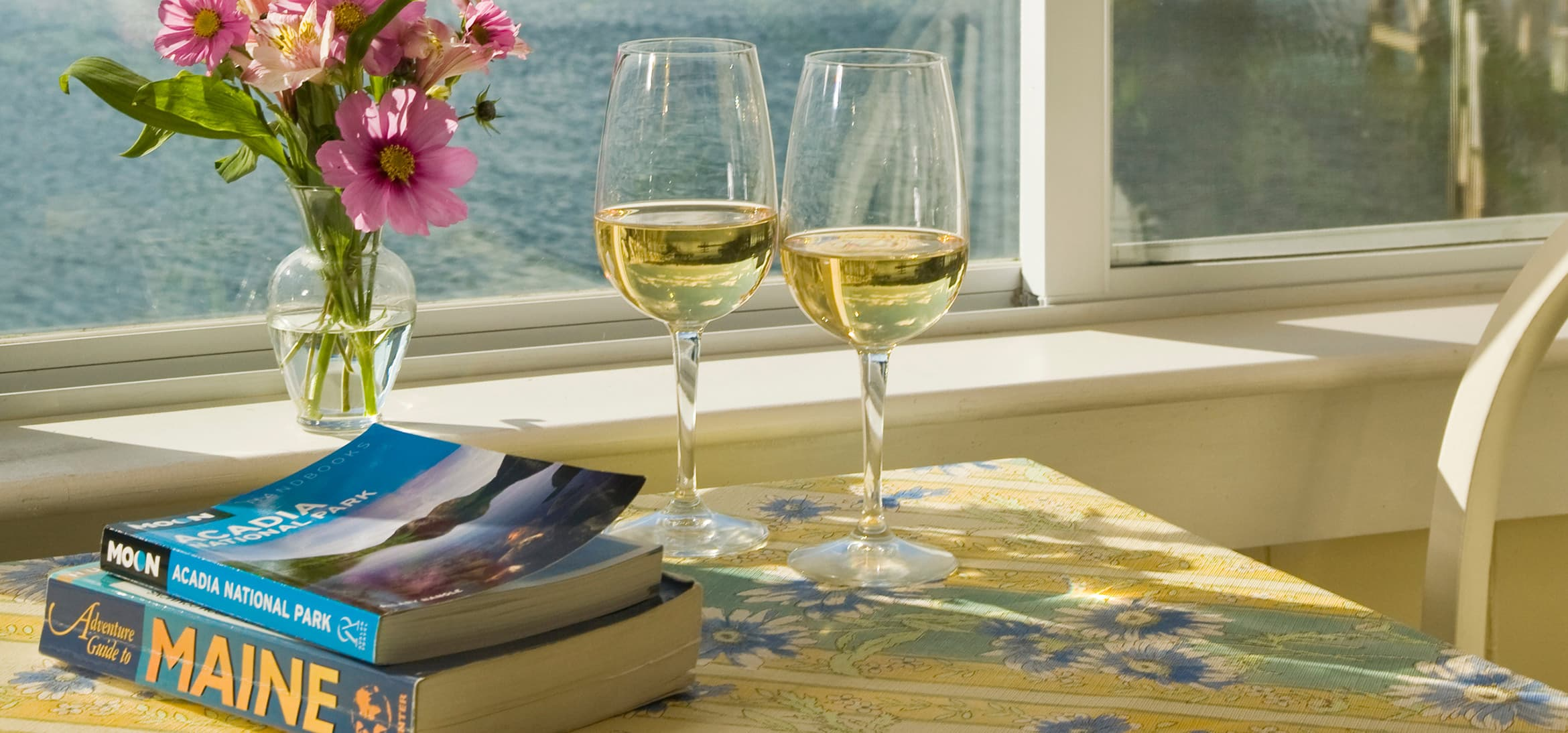 wine glasses on a table next to a Maine guidebook